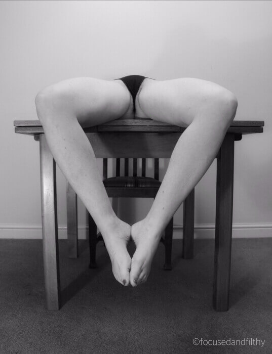 Focused and Filthy lying on table, knees spread, feet pressed together, underwear and thighs exposed