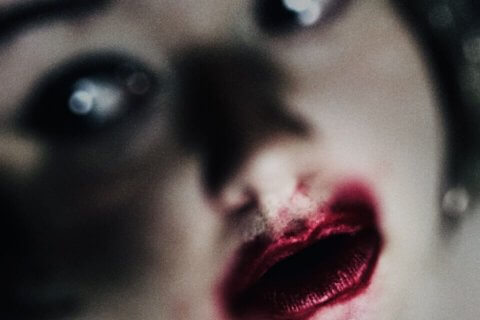 woman's face with blank, glassy eyes and smudged red lipstick like a broken doll - Masturbation Monday prompt 269