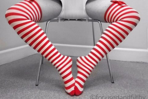 Focused and Filthy sits backwards in a chair wearing Christmas stockings for Masturbation Monday week 274