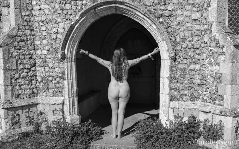 nude woman facing away from camera standing in doorway of old building wearing cuffs and arms stretched out for Masturbation Monday Week 289